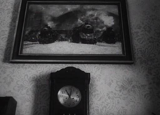 A falon láthatjuk a film két fontos motívumát: a vonatot (festményen) és az órát.