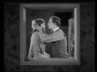 A gépterem ablakán keresztül kukucskálva a vászonról lesi el a film zárójelenetéből a hősszerelmes mozdulatait, amint az átöleli és megcsókolja hölgyét