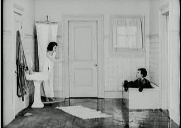 éppen a fürdőkádba esik bele. A feleség már a zuhanyozófüggönybe burkolózik,
