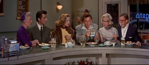 1.61: <em>Hogyan fogjunk milliomost?</em> (<em>How to Marry a Millionaire</em>. Jean Negulesco, 1953): Egy bárban összegyűlt három pár látható szélesvásznon, ahol a semmirekellő felfedi, hogy valójában dúsgazdag.