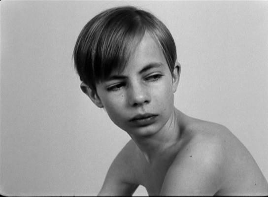 A kisfiú felkel az ágyból és lassan a kamera felé fordul, de nem néz bele.