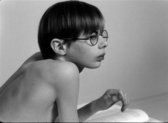 A kisfiú lassú, finom mozdulatokkal felveszi a szemüvegét, majd szembefordulva a kamerával kinyújtja a kezét felé.