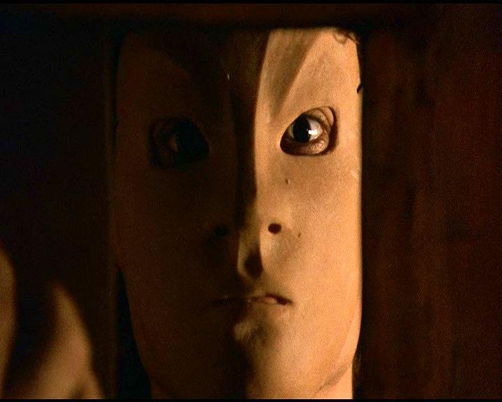 Az Egérfogó egyik maszkos színésze igazgatja a maszkját a kémlelőnyílás tolóajtajának túloldalán lévő tükörben.