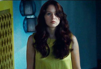 Katniss óarany színű blúzban az azonos színű ágykeret mellett.